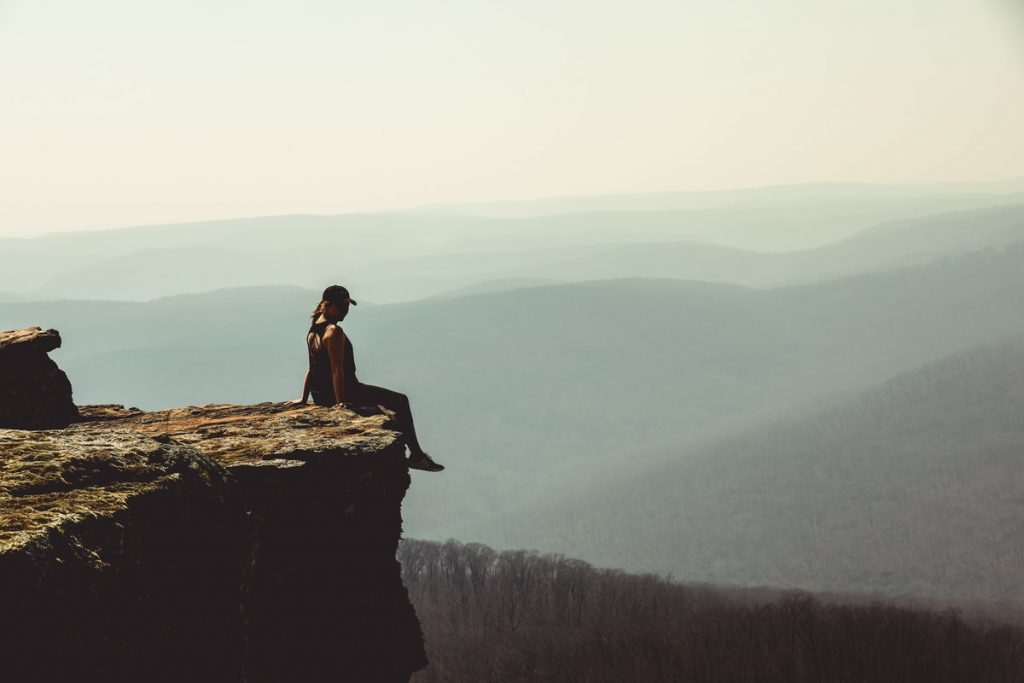 woman-sitting-on-edge-of-rock-formation-1202821